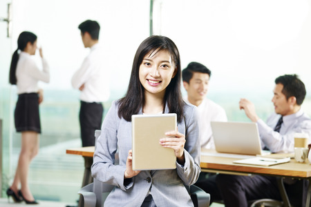 portrait of young asian business woman holding digital tablet looking at camera smiling in office.