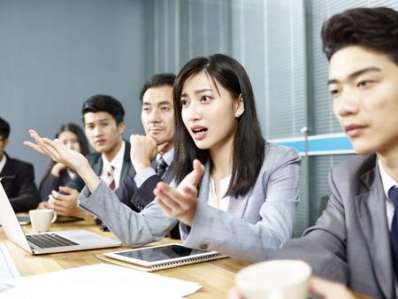 wykonawczy młody azjatycki biznes kobieta angażuje się w ożywioną dyskusję podczas spotkania.