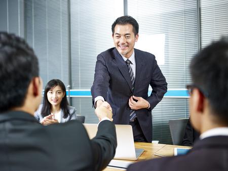 Dos hombres de negocios asiáticos dándose la mano sobre la mesa de reuniones antes de la negociación.