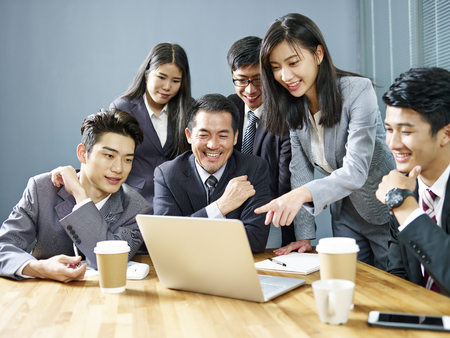 a team of asian business executives working together in office using laptop computer, happy and smiling.
