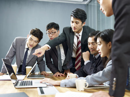 a team of asian business executives men and women working together in office using laptop computer.