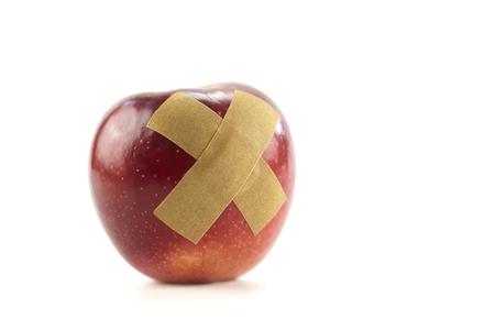 red apple with bandage isolated on white background.