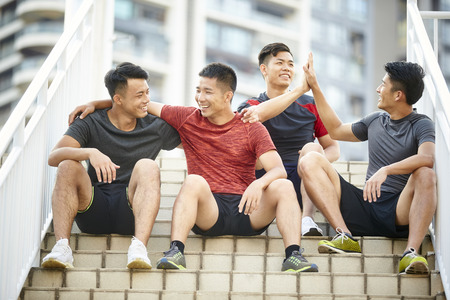 outdoor portrait of a team of four asian young athletes sitting on steps Reklamní fotografie