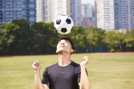 asian soccer football player practicing ball skill on outdoor field Фото со стока