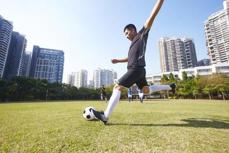 jonge aziatische voetballer die de bal schiet tijdens de wedstrijd