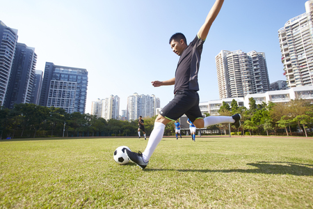 young asian soccer football player shooting the ball during match 写真素材
