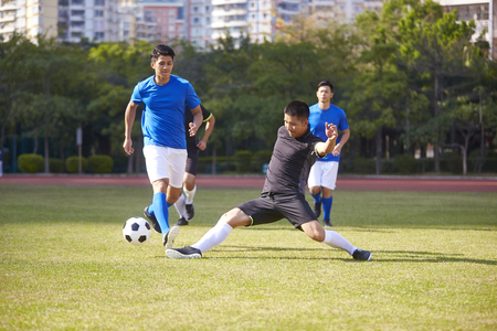 a group of young asian soccer football player playing on outdoor court.