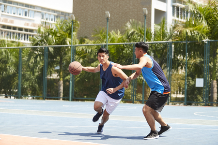 two young asian basketball players playing one on one on outdoor court. Reklamní fotografie