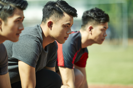young asian track and field athletes sprinters setting on starting line. Foto de archivo