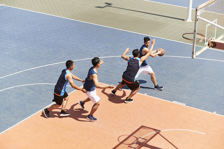 young asian male basketball players playing a game on outdoor court.
