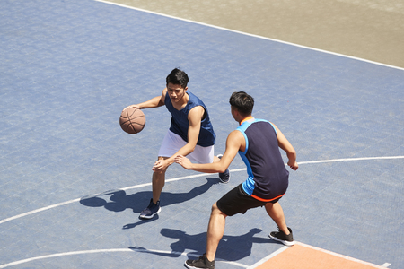 two young asian basketball players playing one on one on outdoor court. Фото со стока