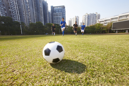 young asian soccer football players chasing the ball during a match Stockfoto