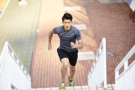 young asian man training running on steps outdoors