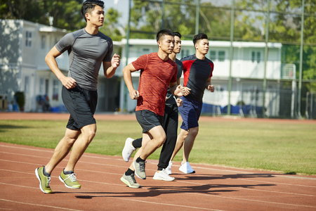 four young asian track and field athletes racing competing against each other. Banco de Imagens