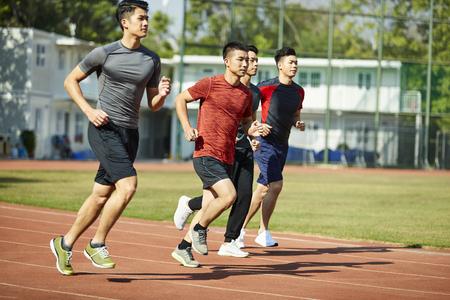 quatre jeunes athlètes asiatiques d'athlétisme s'affrontant les uns contre les autres.