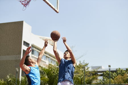 young asian basketball player shooting the ball over defender on outdoor court.