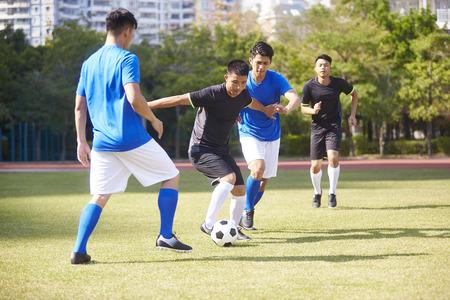 grupa młodych azjatyckich piłkarzy piłki nożnej grających na korcie na świeżym powietrzu.
