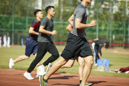 four young asian track and field athletes racing competing against each other. 写真素材