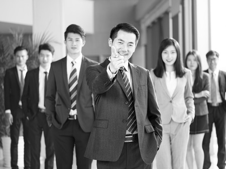 portrait of a team of successful asian businessmen and businesswomen, pointing and looking at camera smiling, black and white. Stock Photo