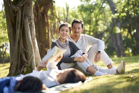 Zwei asiatische Kinder, kleine Jungen und Mädchen, die Spaß haben, auf Gras zu liegen und ein Buch zu lesen, während die Eltern im Hintergrund sitzen und beobachten.