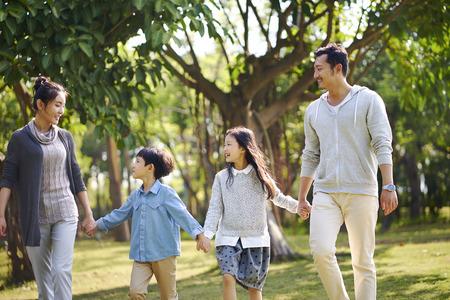 famiglia asiatica con due bambini che camminano rilassandosi nel parco felici e sorridenti.