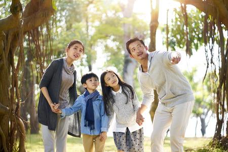 aziatische familie met twee kinderen die plezier hebben in het verkennen van bossen in een park. Stockfoto