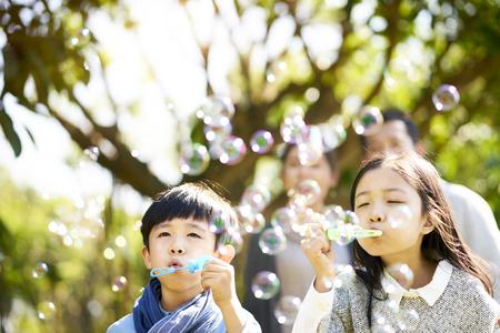 작은 아시아 어린이 소년과 소녀 자매와 형제는 뒤에서 지켜보는 부모와 함께 공원에서 거품을 불고 있습니다.