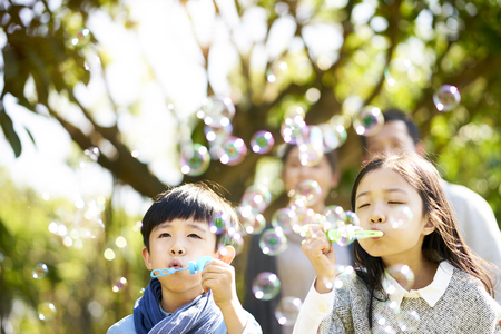 little asian kids boy and girl sister and brother blowing bubbles in a park with parents watching from behind. Banco de Imagens