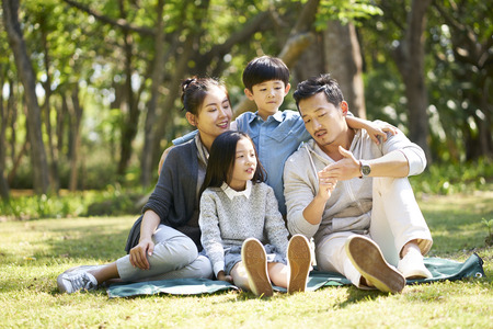 asian family with two children having fun sitting on grass chatting at park