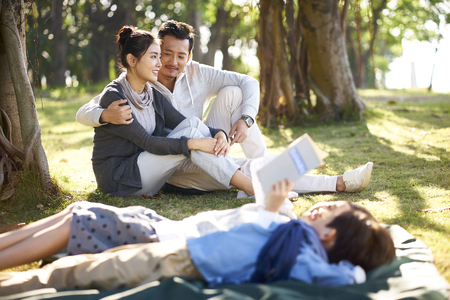 young asian couple sitting on grass in park chatting with two children lying reading book in foreground.