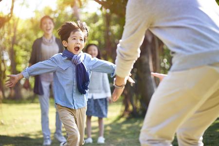 figlio del ragazzino asiatico che corre verso l'abbraccio del padre. Archivio Fotografico