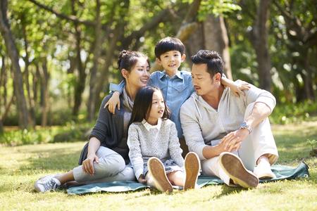 famiglia asiatica con due bambini che si divertono seduti sull'erba a parlare chiacchierando all'aperto nel parco