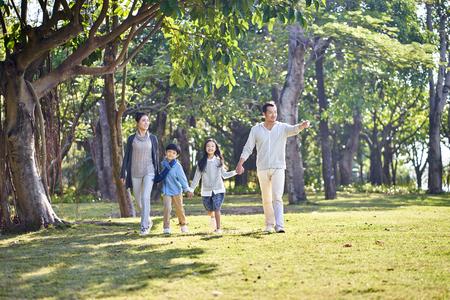 Aziatische familie met twee kinderen die hand in hand buiten in het park lopen.