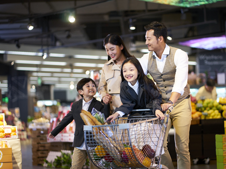 happy asian family with two children shopping in supermarket 스톡 콘텐츠