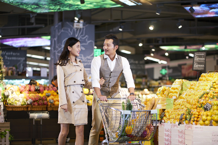 happy young asian couple shopping in supermarket Imagens