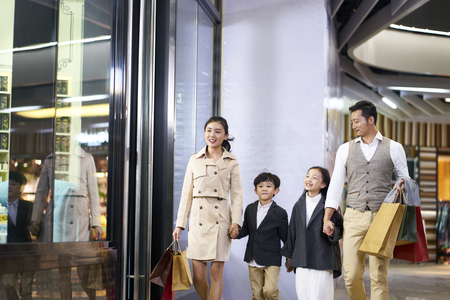 happy asian family with two children walking in shopping mall Stock Photo