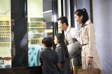 Feliz familia asiática con dos niños mirando a un escaparate en el centro comercial