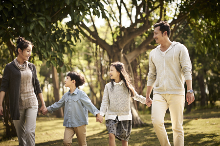 asian family with two children walking relaxing in park happy and smiling. Stockfoto
