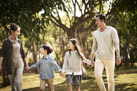 famille asiatique avec deux enfants marchant se détendre dans le parc heureux et souriant.