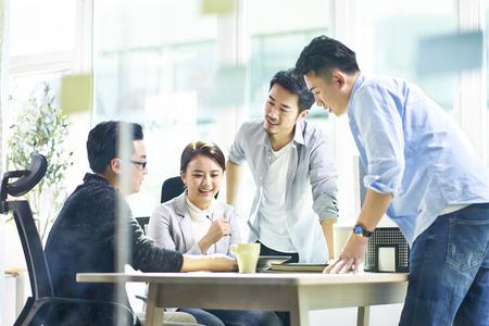 Grupo de cuatro ejecutivos corporativos asiáticos jóvenes felices trabajando juntos reunidos en la oficina discutiendo negocios en la oficina.