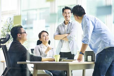 Gruppe von vier glücklichen jungen asiatischen Firmenkollegen, die sich treffen, um Geschäfte im Büro zu besprechen.