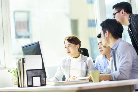 Cuatro jóvenes empresarios asiáticos reunidos en la oficina discutiendo el plan de negocios con PC de escritorio.