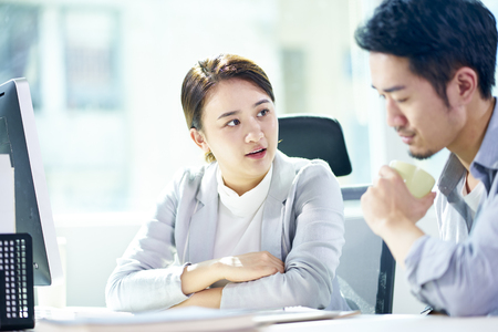 asian businessman and businesswoman working together in office discussing business plan.