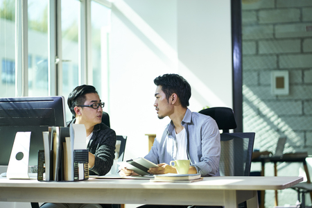 two young asian corporate executives working together discussing business plan in office. 版權商用圖片
