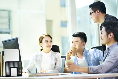 vier jonge Aziatische zakenmensen ontmoeten elkaar op kantoor en bespreken het businessplan met behulp van tablet-pc. Stockfoto