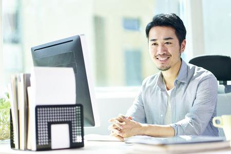 jeune homme d'affaires asiatique assis par bureau devant un ordinateur de bureau regardant la caméra en souriant.