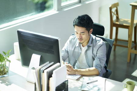 young asian business man entrepreneur sitting at desk in office contemplating.
