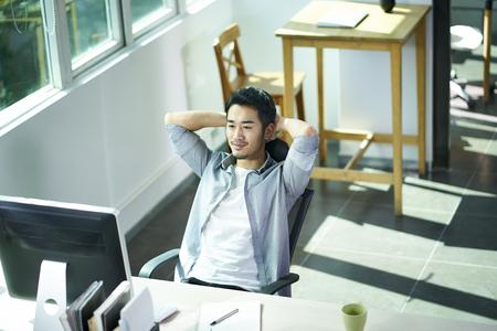 junger asiatischer Geschäftsmann, der mit Zufriedenheit auf den Computermonitor schaut, die Hände hinter dem Kopf.