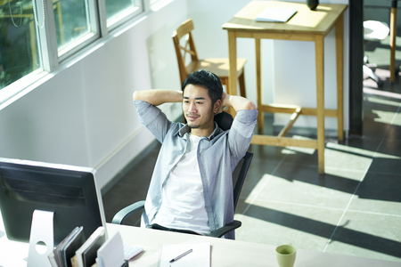 young asian business man looking at computer monitor with satisfaction, hands behind head. Standard-Bild