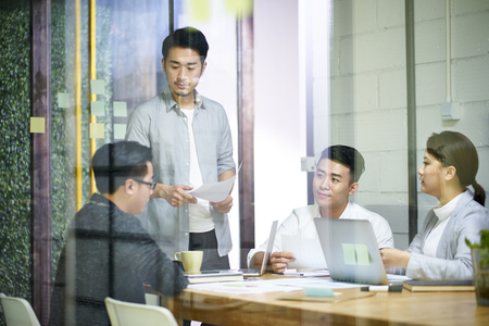 young asian entrepreneurs of small company discussing business plan in office meeting room. Standard-Bild - 120258025